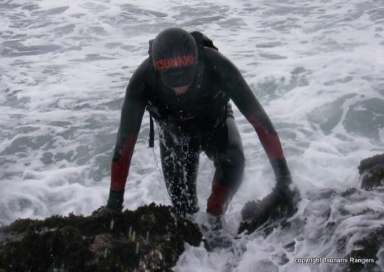 Eric Soares emerges from the surf wearing a full wetsuit and neoprene hood