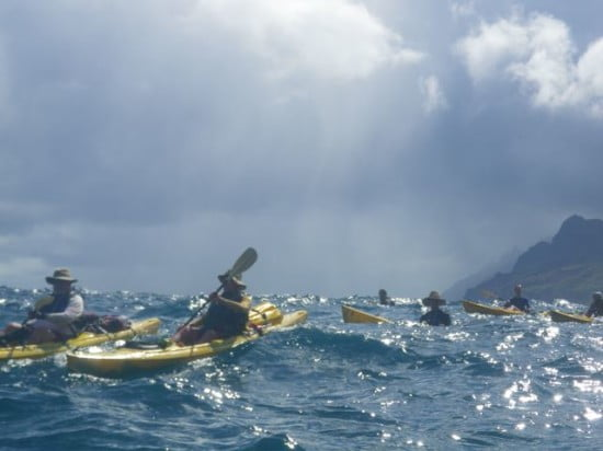 Paddling with rain showers as the group heads to Polihale State Park for one more crashing surf landing